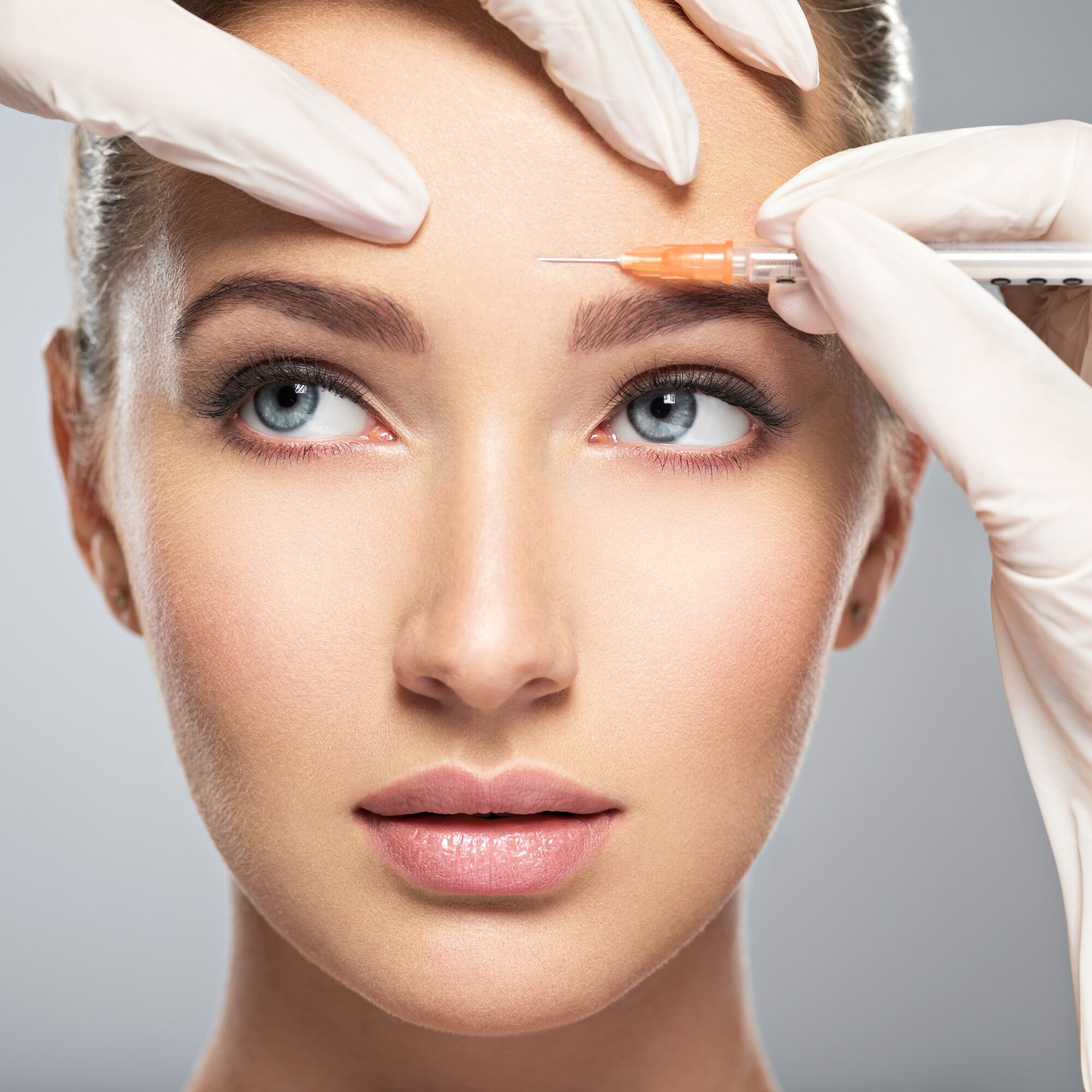 Woman getting botox injected into her forehead