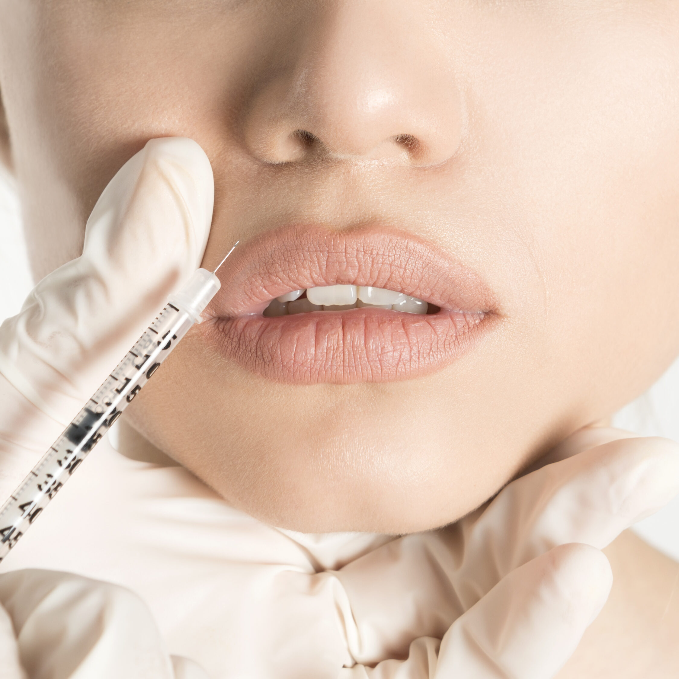 Woman having filler injected into her lips